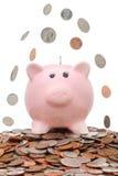 fallande pengar för grupp över piggy Arkivbilder