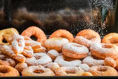 Fallande pudrat socker på nya hemlagade donuts Fotografering för Bildbyråer