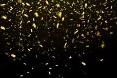 Fallande skinande guld blänker konfettier som isoleras på svart bakgrund Arkivfoto