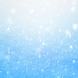 Fallande snö för konst på den blåa bakgrunden Royaltyfri Foto