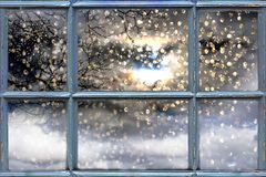 Fallande snö utanför fönstret arkivfoto
