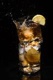Fallande stycke av is i ett högkvalitativt exponeringsglas av whisky med färgstänk som står på ett annat exponeringsglas som är f Royaltyfri Bild