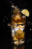 Fallande stycke av is i ett högkvalitativt exponeringsglas av whiskyanseende på ett annat exponeringsglas som är fullt av is- och Arkivbilder