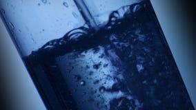 Fallande vatten i ett exponeringsglas arkivfilmer
