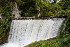 Fallande vattenströmmar av en gammal kraftverk dämmer av vattenfallet Royaltyfria Bilder