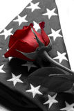 Fallen. A lone red rose sits on top of an american flag. Honor respect Royalty Free Stock Image