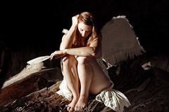 Fallen Angel. Low key image of a fallen beautiful sad angel holding a feather Stock Photo