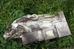 Fallen angel. Destroyed tombstone at the abandoned cemetery. Royalty Free Stock Photo