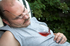 Fallen asleep. Mature man in the garden having fallen asleep from drinking too much Royalty Free Stock Image