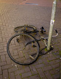 Fallen bike. A fallen bike chained to a post on a paved street in Amsterdam Royalty Free Stock Photography