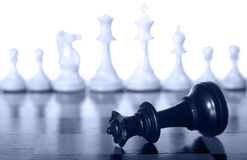 Fallen black chess queen. Chess queen on a chessboard as a business concept with out of focus chessmen Royalty Free Stock Image