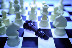 Fallen chess piece. A toppled black king chess piece is surrounded by various white chess pieces on a chessboard royalty free stock photo