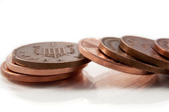Fallen coins. Close and low level capturing a fallen stack of British copper pennies arranged on white stock image