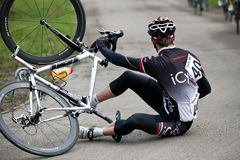 Fallen cyclist. MILTON KEYNES, ENGLAND - MARCH 17: An unnamed rider of the iCycle team slides off on the wet surface during the semi- pro 2/3 Band 4 cycling race Stock Images