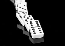 Fallen dominoes lying on black shining surface Stock Photos