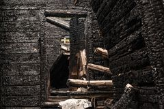 Fallen down burned wooden house stock photography