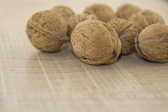 Walnuts on a wooden base. Fallen fruits, nuts in a shell on a wooden base Stock Photo