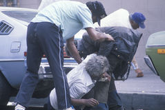 Fallen homeless man in city street getting help, Los Angeles, California Stock Photography