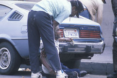 Fallen homeless man in city street getting help, Los Angeles, California Stock Images