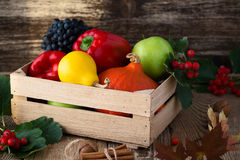 Fallen leaves, winter squash and vegetables in a wooden box. Fal Stock Photo