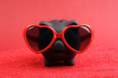Fallen in love black piggy bank with red heart sunglasses standing on red sand in front of red background Royalty Free Stock Images