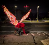Fallen male angel with fire wings. Fallen male angel kneeling in city parking lot, with fire wings spreading from his back. Unrecognizable young man stock photo