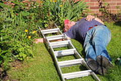 Fallen man from ladder unconscious. An elderly man lying unconcious on the ground after having fell from a ladder Royalty Free Stock Photo