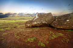 Fallen moai in Easter Island. Fallen moai on red earth with mountain on background royalty free stock photography