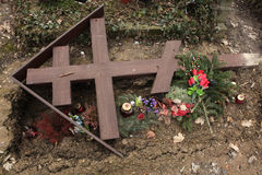 Fallen orthodox cross on an unmarked grave. Stock Images