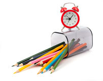 Fallen pencil cup with crayons and alarm clock Stock Photo