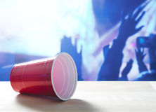 Fallen plastic red party cup on its side on a table. Nightclub or disco full of people dancing on the dance floor. Stock Photo