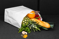 Fallen shopping bag at car boot - interior. Pineapple, baguette, orange, paprika and leek are out of the bag. An egg crashed near bag. Shopping were spilled Royalty Free Stock Photos