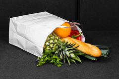 Fallen shopping bag at car boot - interior. Pineapple, baguette, orange, paprika and leek are out of the bag. Shopping were spilled Royalty Free Stock Image