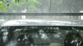 Fallen und Wasser des starken Regens spritzend auf Dachauto im Parken stock video footage