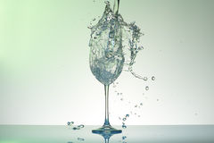 Fallen water with blue tint pouring into a big size wineglass with many splashes. Royalty Free Stock Image