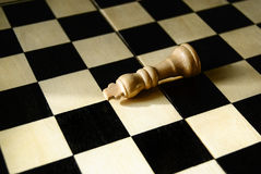 Fallen king concept. Fallen white wooden king on empty chess board Royalty Free Stock Photos