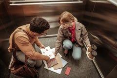 Fallende Dokumente der unaufmerksamen Frau auf dem Boden im Aufzug lizenzfreie stockfotografie