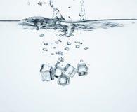 Fallende Eiswürfel im Wasser Stockfotografie