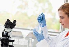 Fallende Flüssigkeit des Wissenschaftskursteilnehmers in einem Becher stockbild