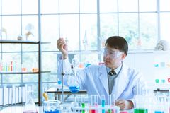 Fallende Fl?ssigkeit des Wissenschaftlers in blaues Reagenzglas lizenzfreies stockbild