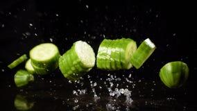 Fallende Gurkenschnitte mit Wasserspritzen, Zeitlupe stock footage