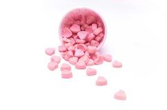 Fallende Herzsüßigkeit in den Papierschalen des rosa Tupfens lokalisiert lizenzfreies stockbild