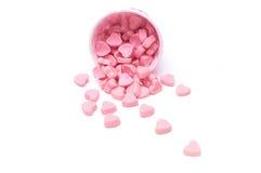 Fallende Herzsüßigkeit in den Papierschalen des rosa Tupfens lokalisiert stockbild
