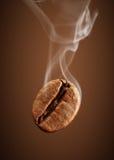 Fallende Kaffeebohne der Nahaufnahme mit Rauche auf braunem Hintergrund Stockbilder