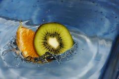 Fallende Kiwi und orange Frucht in das Wasser mit einem schönen Spritzen stockbild