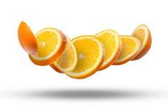 Fallende Scheiben der Orange in einer Luft auf Weiß Lizenzfreie Stockbilder