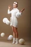 Fallende Stränge. Überraschte Frau im Woolen Strickpulli mit weißen Bällen des Garns Lizenzfreie Stockbilder