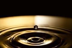 Fallende Wasserblase Ringe bewegt in dunkle Bronze und in schwarzen spritzenden Hintergrund wellenartig Makroansicht, Weichzeichn Stockfoto