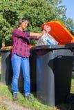 Fallender Abfall der stehenden niederländischen Frau Plastikim Abfalleimer Stockfotos