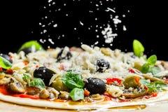 Fallender Käse auf einer frisch zubereiteten Pizza mit schwarzen Oliven Stockbilder